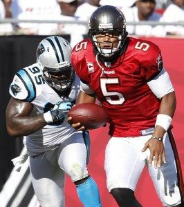 Tampa Bay Buccaneers quarterback Josh Freeman runs upfield chased by Carolina Panthers defensive end Charles Johnson uring the first half of their NFL football game in Tampa