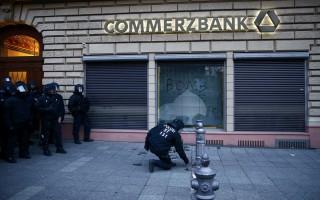 Un policía antidisturbios inspecciona una ventana rota  de Commerzbank (Foto: Reuters)
