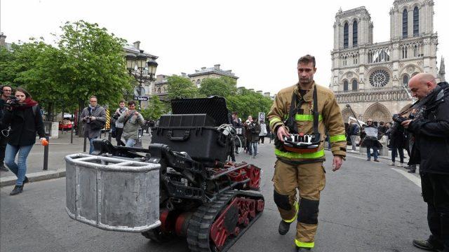 El robot Colossus junto a bombero parisino. Foto Reuters.