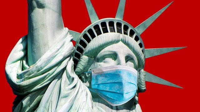 Coronavirus COVID-19 in USA. Statue of Liberty in a medical mask
