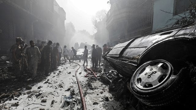 Pakistán Rescue workers gather at the site of a passenger plane crash in a residential area near an airport in Karachi