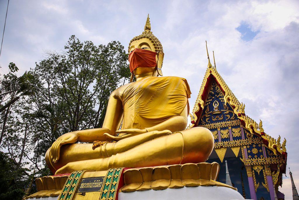 Coronavirus Buddha statue of Nidharat Pradit temple wears a face mask