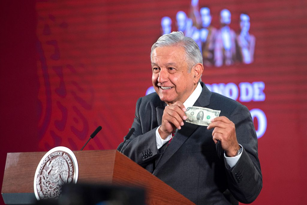 Mexico's President Andres Manuel Lopez Obrador shows a two dollar bill, which he says serves him as a ?protective shield? against the coronavirus disease (COVID-19), during a news conference in Mexico City