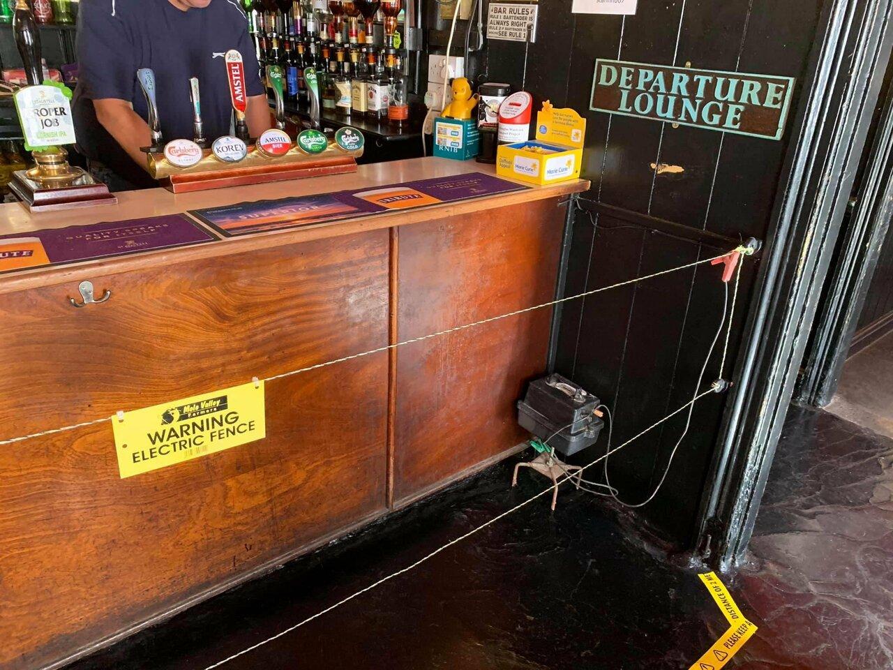 Bar inglés recibe a clientes con valla eléctrica para obligar distanciamiento