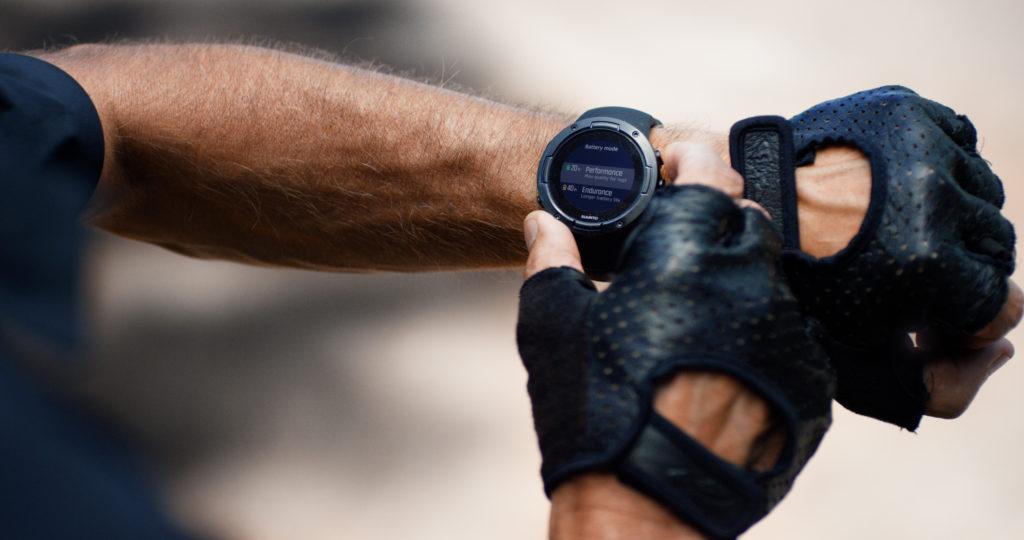 manos con guantes negros Suunto smartwatches