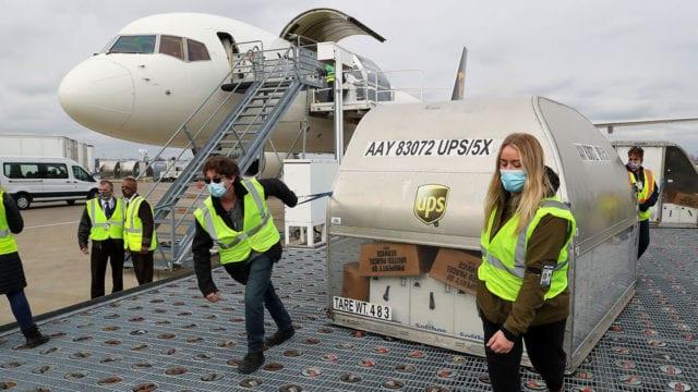 Los empleados de UPS mueven uno de los dos contenedores de envío de la vacuna Pfizer COVID-19 en la rampa del Aeropuerto Internacional Louisville Muhammad Ali en Louisville, Kentucky, EE. UU