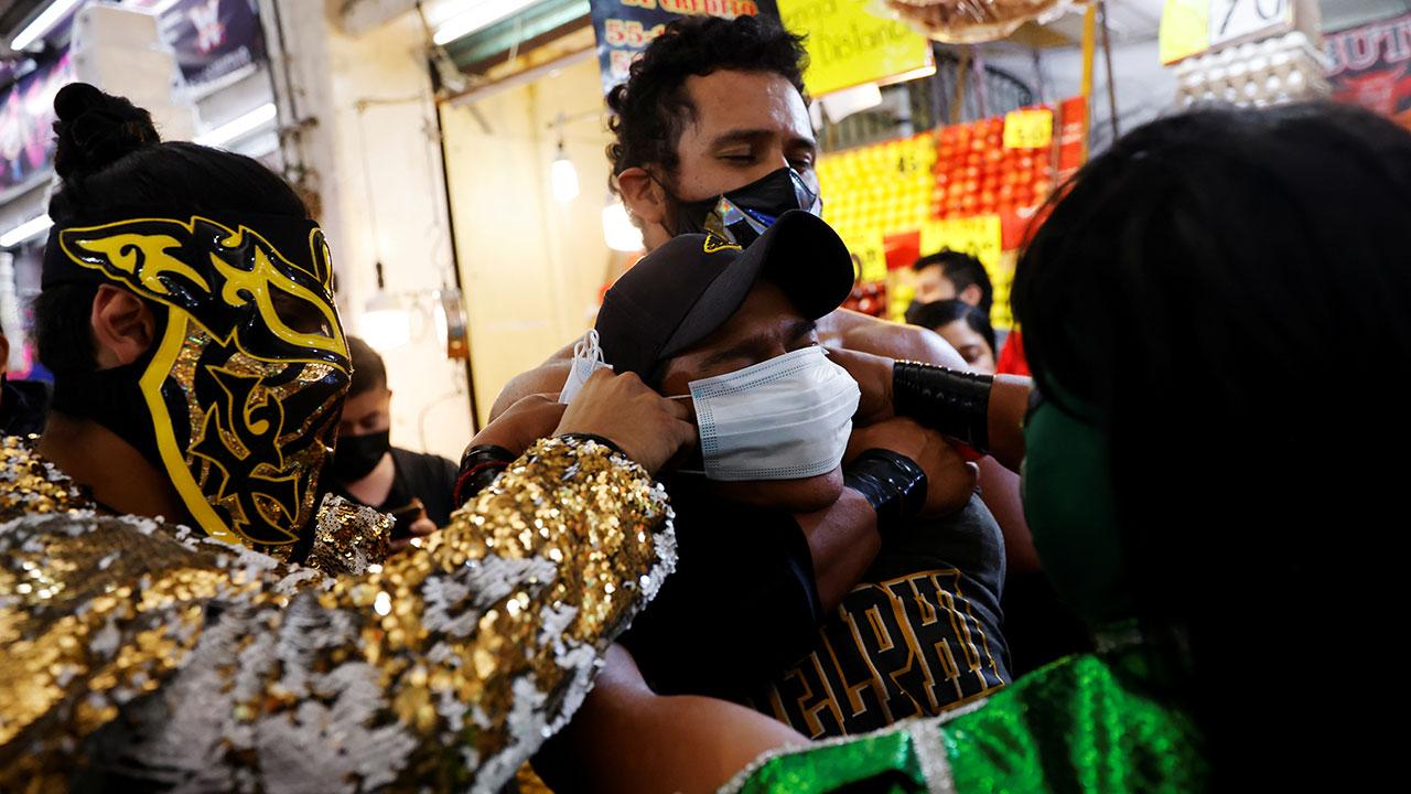 Mascarillas a la fuerza: luchadores reparten cubrebocas en el metro